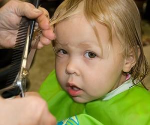 Madre cortando el pelo por piojos
